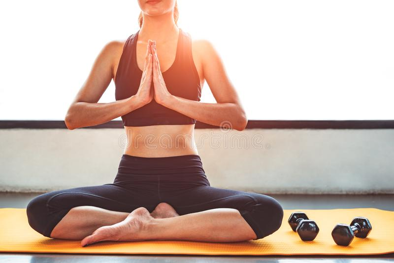 Mujer de la belleza de la vista delantera que hace yoga y aumentar la mano o pagar deferencia en los entrenamientos de la aptitud imagenes de archivo