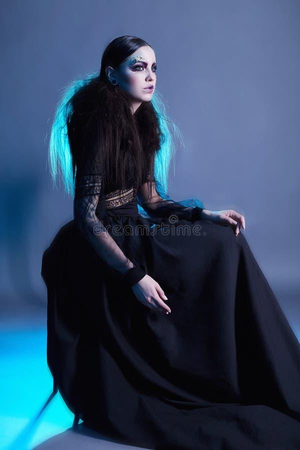 Mujer de la bruja de la moda con el maquillaje de Halloween imagenes de archivo