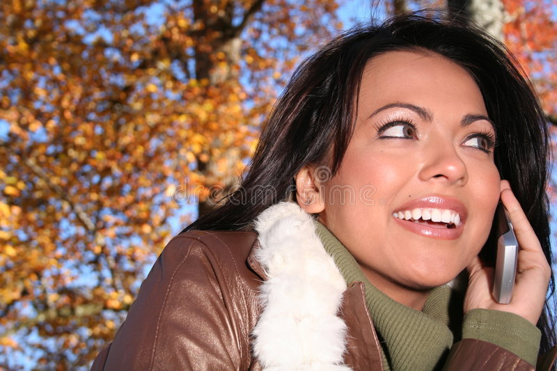 Mujer de la caída de la escena del otoño con el teléfono celular fotos de archivo libres de regalías