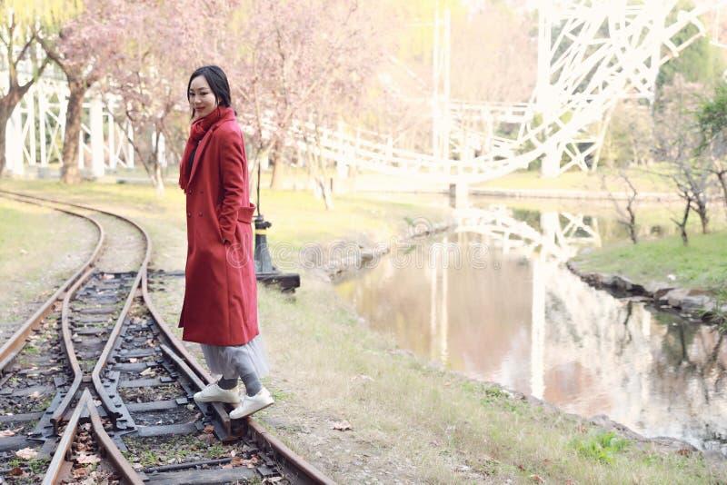 Mujer de la caída feliz y dicha, muchacha hermosa de la mujer que camina en el ferrocarril en parque del otoño imagen de archivo libre de regalías
