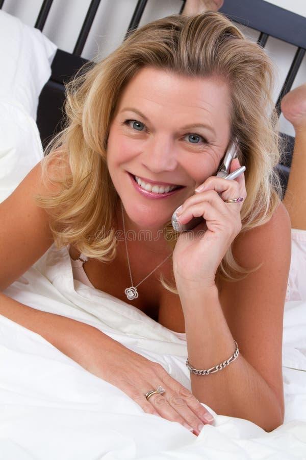 Mujer de la cama del teléfono imagen de archivo
