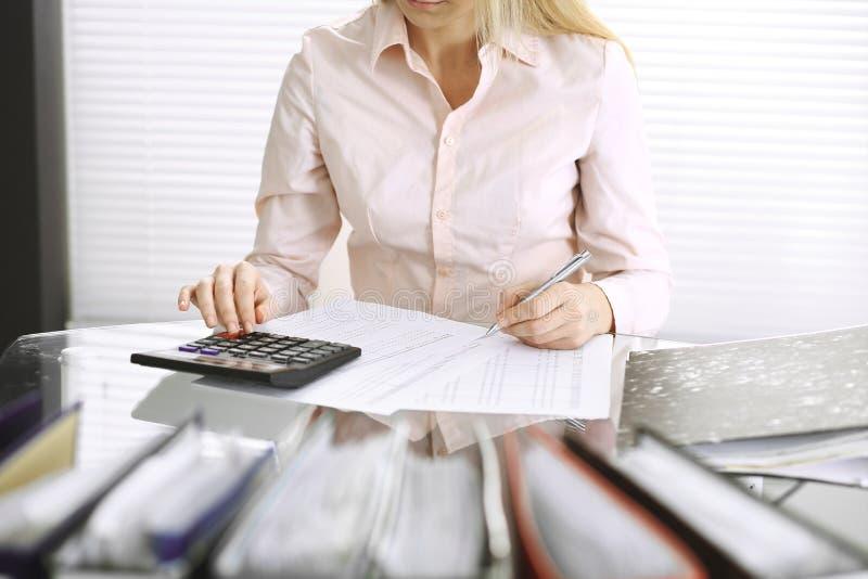 Mujer de la contable o inspector financiero que hace informe, calculando o comprobando la balanza, primer Negocio, auditor?a o im imagen de archivo libre de regalías