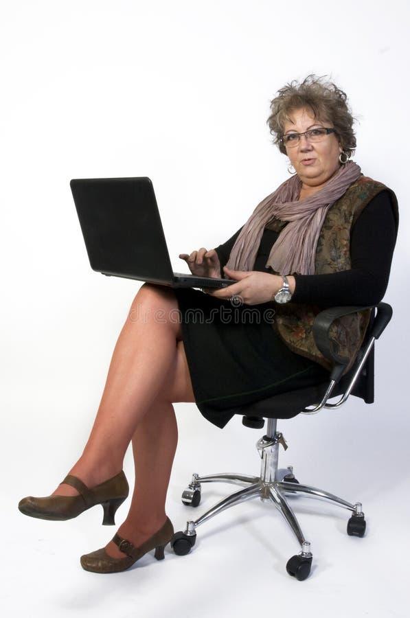 Mujer de la Edad Media con la computadora portátil fotografía de archivo libre de regalías