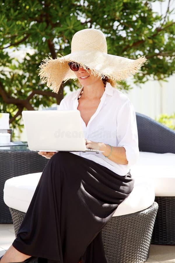 Mujer de la Edad Media con la computadora portátil imágenes de archivo libres de regalías