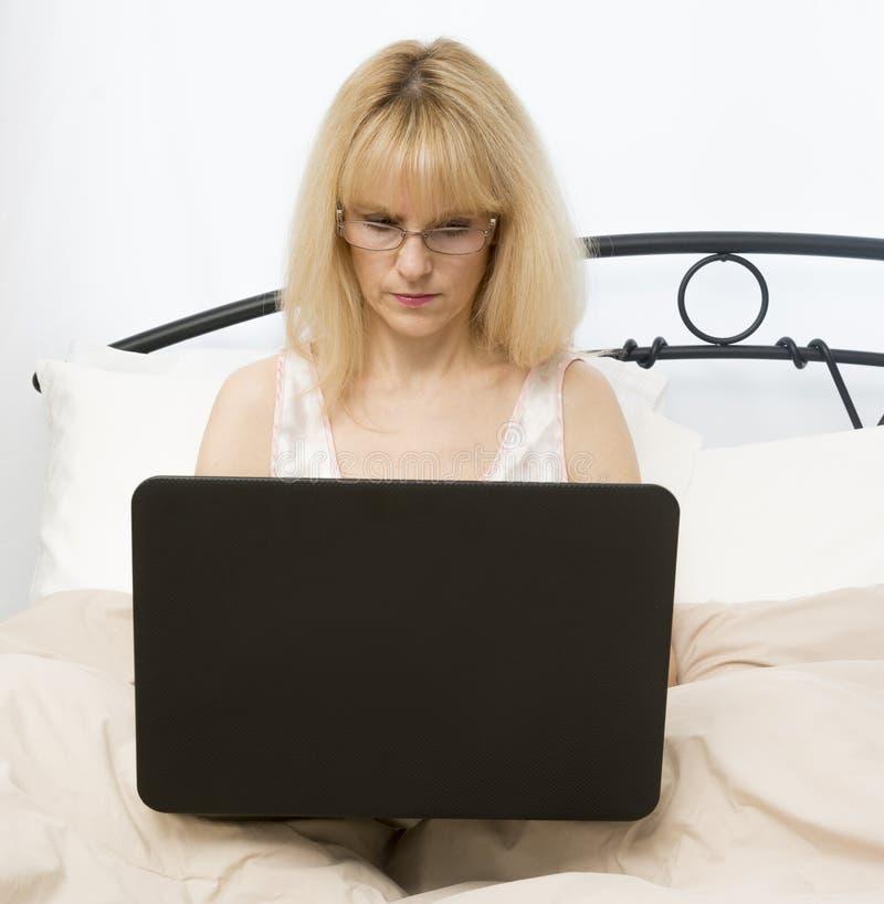 Mujer de la Edad Media en cama usando el ordenador portátil fotos de archivo libres de regalías
