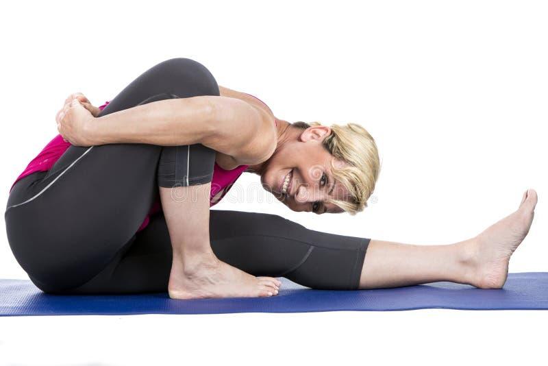 Mujer de la Edad Media que hace ejercicios de la yoga imagen de archivo libre de regalías