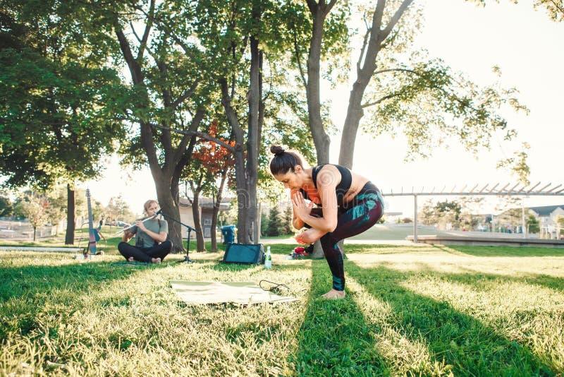 Mujer de la Edad Media que hace yoga en parque afuera en puesta del sol foto de archivo