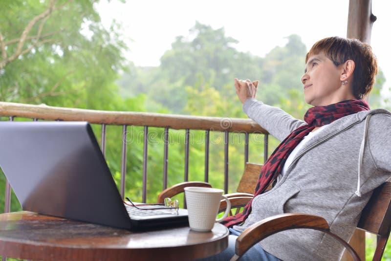 Mujer de la Edad Media que se relaja con el ordenador portátil imagen de archivo