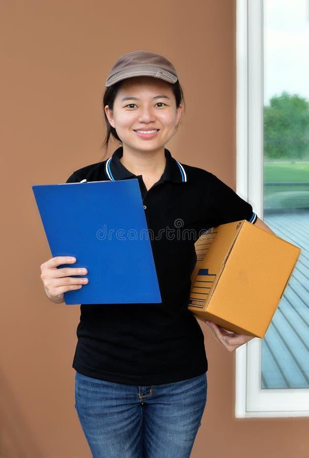 Mujer de la entrega que entrega los paquetes que sostienen el tablero fotografía de archivo libre de regalías