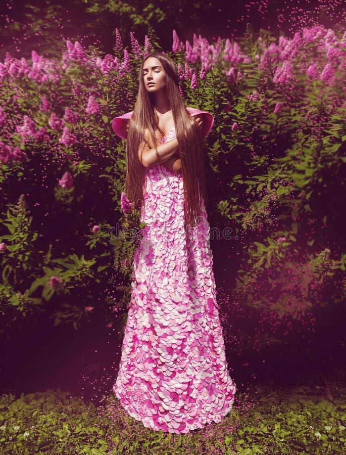 Mujer de la fantasía en vestido rosado largo con las flores fotos de archivo libres de regalías