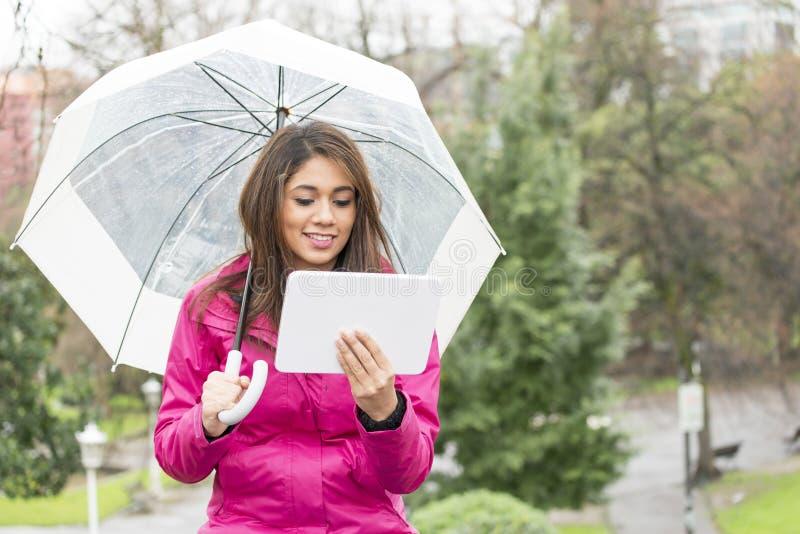 Mujer de la felicidad con el paraguas y la tableta en el parque imágenes de archivo libres de regalías