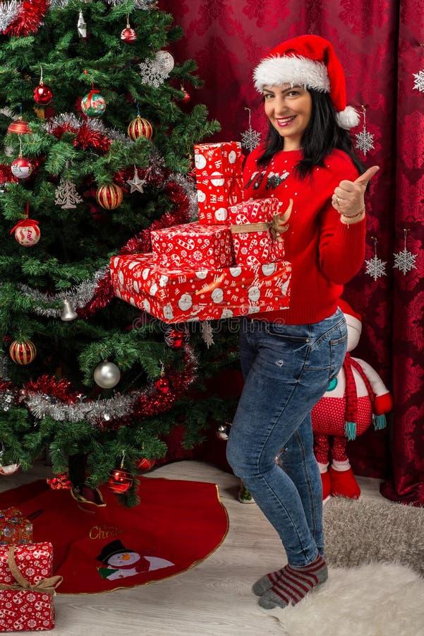 Mujer de la feliz Navidad que da los pulgares foto de archivo