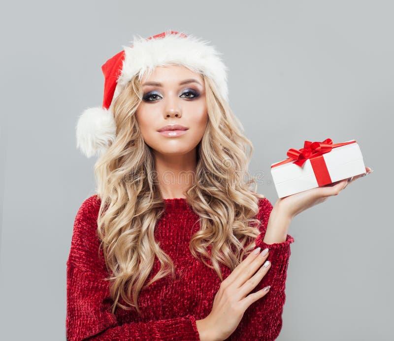 Mujer de la feliz Navidad que muestra la caja de regalo de la Navidad blanca fotografía de archivo libre de regalías