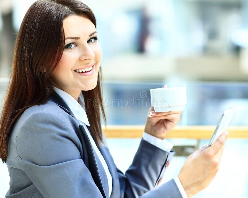 Mujer de la forma de vida de la ciudad del café en el texto que manda un SMS de consumición del café del teléfono foto de archivo libre de regalías