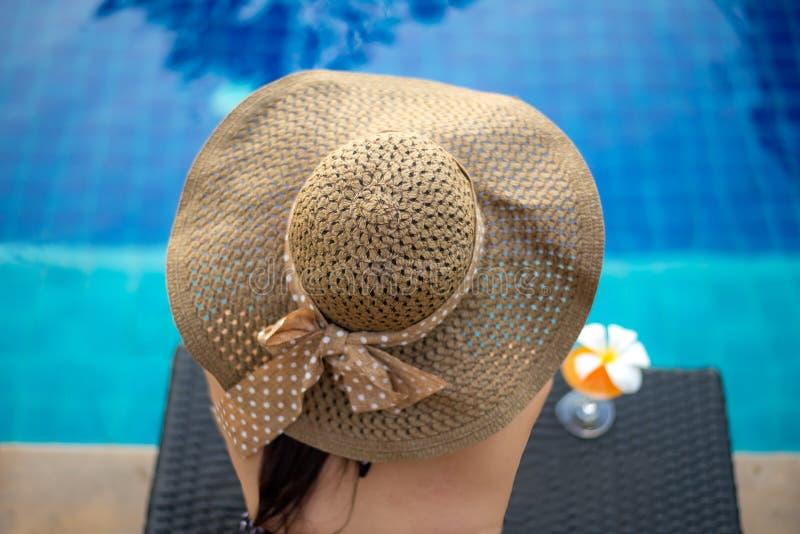 Mujer de la forma de vida en el traje de baño relajante y feliz con el cóctel en el sillón cerca de la piscina, día de verano imagenes de archivo