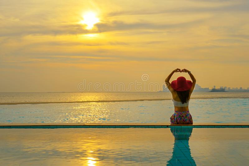 Mujer de la forma de vida feliz en la relajación y la libertad grandes del sombrero en la piscina cerca de la playa del mar en la foto de archivo libre de regalías