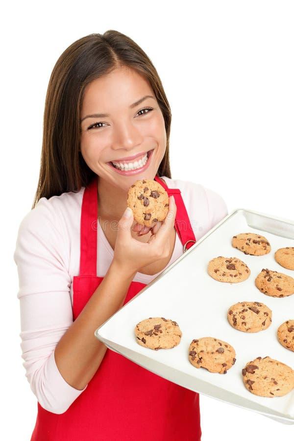 Mujer de la hornada que come las galletas felices fotos de archivo