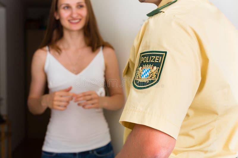 Mujer de la interrogación del oficial de policía en la puerta principal imágenes de archivo libres de regalías