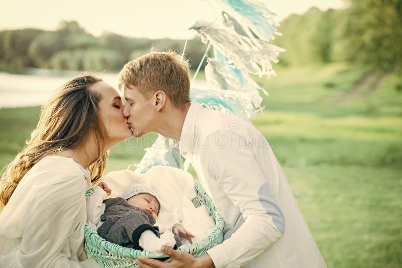Mujer de la madre del beso del hombre del padre con el niño del bebé en pesebre imagenes de archivo