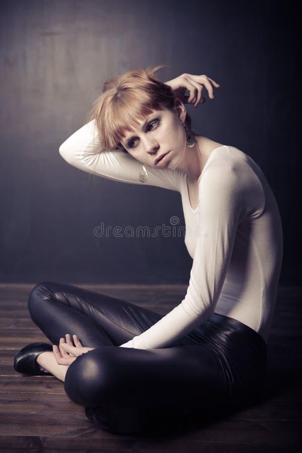 Mujer de la manera que se sienta en un suelo de madera imagenes de archivo