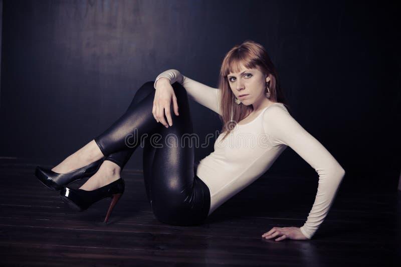 Mujer de la manera que se sienta en un suelo de madera imagen de archivo
