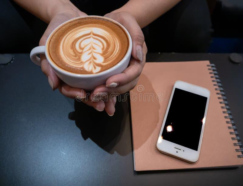 Mujer de la mano que sostiene una taza de caf? caliente de los artes del latte con el tel?fono celular y de nota sobre la tabla n imagen de archivo