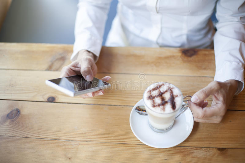 Mujer de la mano que usa el teléfono en café foto de archivo