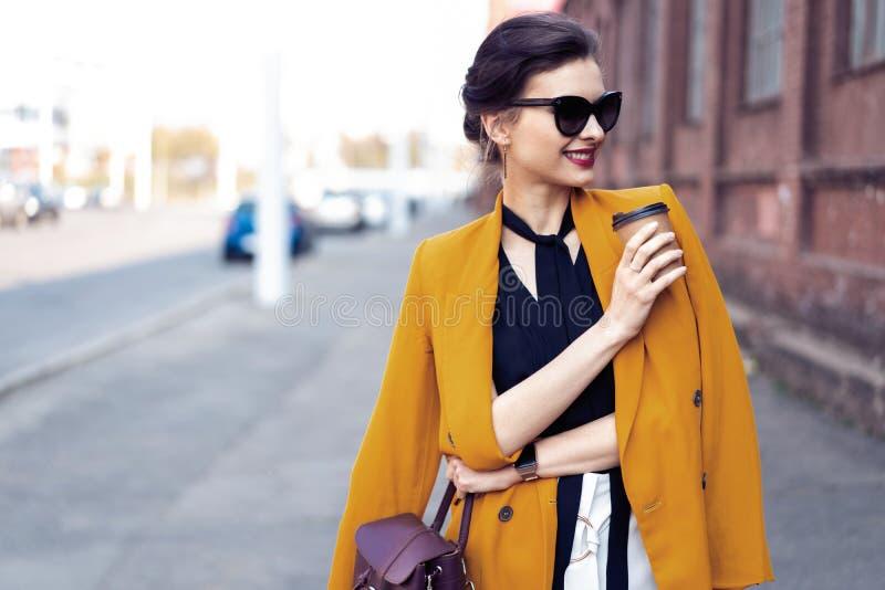 Mujer de la moda del retrato en gafas de sol que camina en la calle Ella lleva la chaqueta amarilla, sonriendo para echar a un la fotos de archivo
