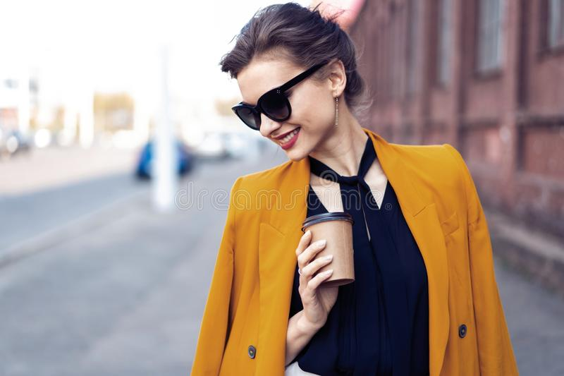 Mujer de la moda del retrato en gafas de sol que camina en la calle Ella lleva la chaqueta amarilla, sonriendo para echar a un la fotos de archivo libres de regalías