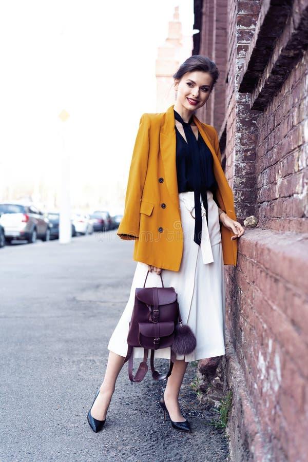 Mujer de la moda del retrato que camina en la calle Ella lleva la chaqueta amarilla, sonriendo para echar a un lado foto de archivo