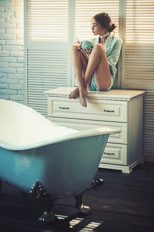 Mujer de la moda en chaqueta en el baño La mujer se sienta en cajón en cuarto de baño La muchacha de la belleza come la comida de fotografía de archivo libre de regalías