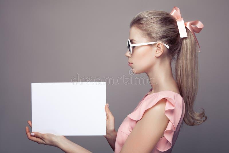 Mujer de la moda en gafas de sol con el espacio en blanco de papel vacío en manos fotografía de archivo