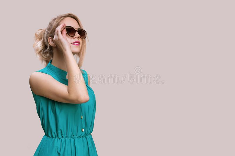 Mujer de la moda en gafas de sol en un fondo gris imagen de archivo libre de regalías