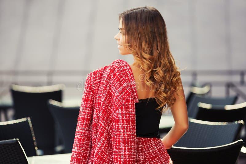 Mujer de la moda de los jóvenes en chaqueta y traje chaqueta rojos de tweed en el café de la acera fotos de archivo