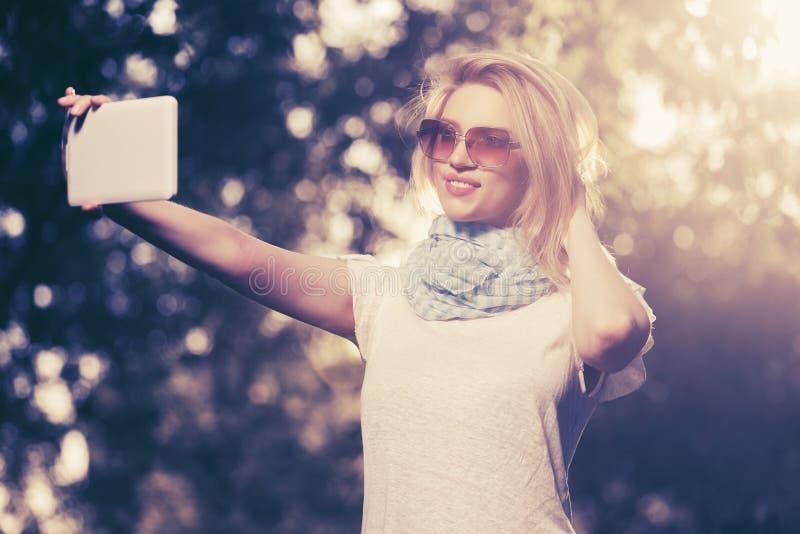 Mujer de la moda de los jóvenes que toma un selfie con la tableta al aire libre fotografía de archivo