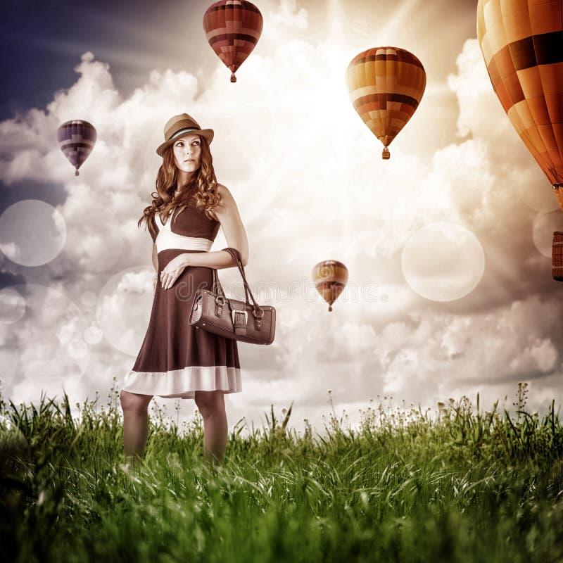 Mujer de la moda que mira a los aerostatos que vuelan fotos de archivo