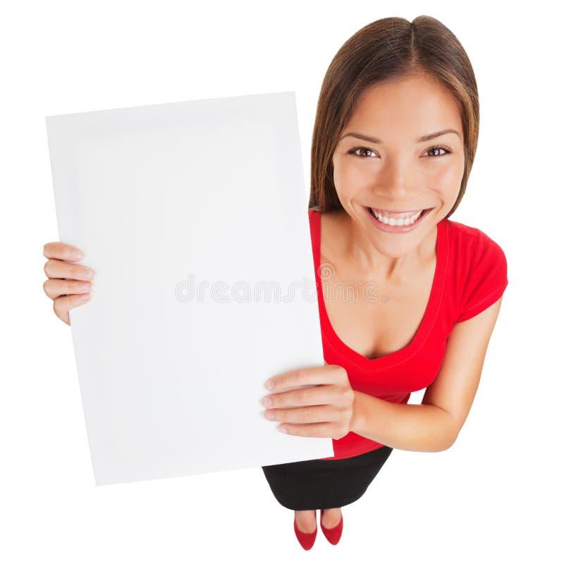 Mujer de la muestra que soporta un cartel blanco en blanco fotos de archivo