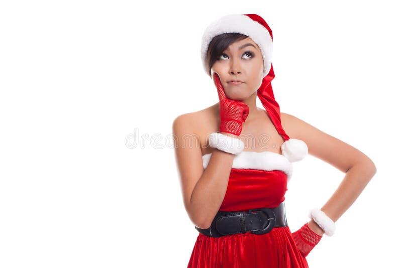 Mujer de la Navidad de Papá Noel que mira al pensamiento del lado feliz y al pla imagenes de archivo