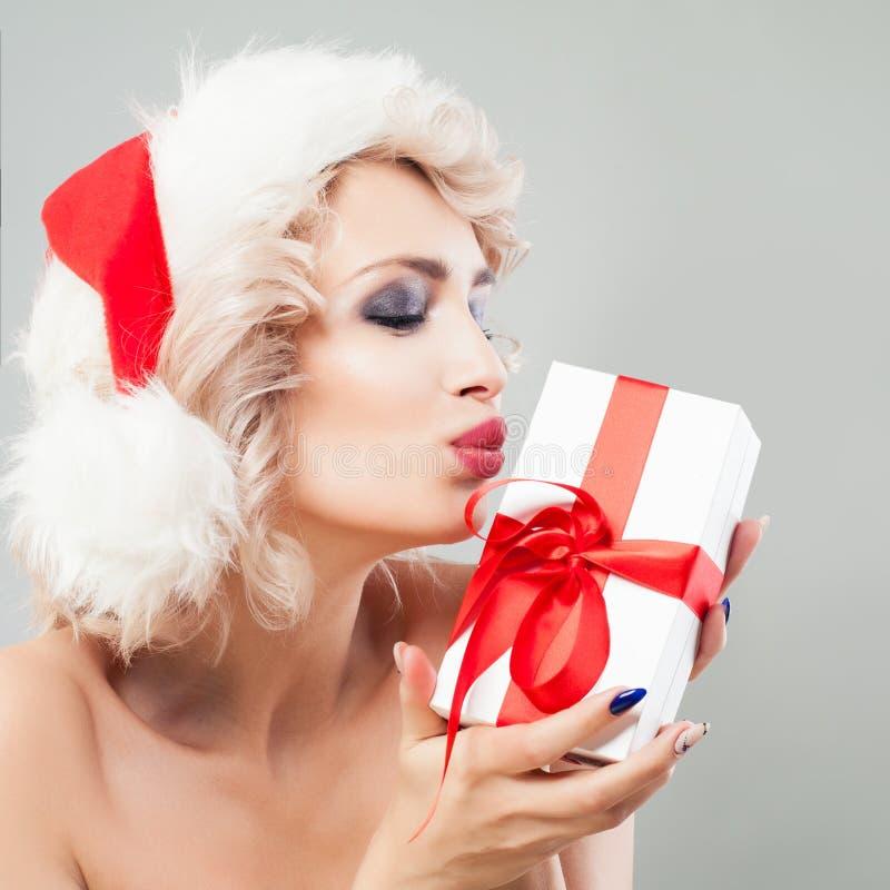 Mujer de la Navidad en caja de regalo de Santa Hat Kissing White Xmas foto de archivo