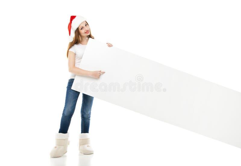 Mujer de la Navidad en el sombrero de santa que señala al tablero vacío fotografía de archivo libre de regalías