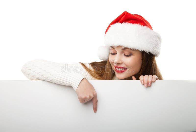 Mujer de la Navidad en el sombrero de santa que señala al tablero vacío imagen de archivo libre de regalías