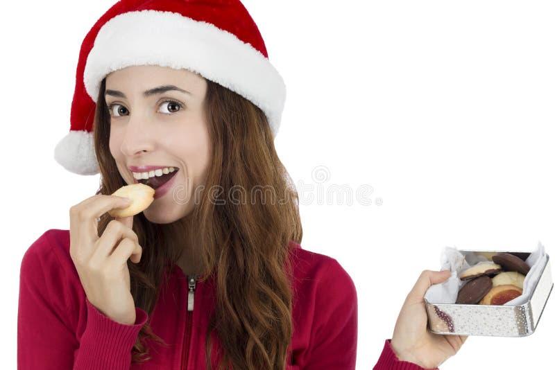 Mujer de la Navidad que come las galletas de la Navidad imágenes de archivo libres de regalías
