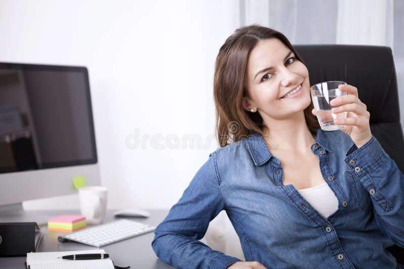 Mujer de la oficina en su silla con el vidrio de agua imagenes de archivo