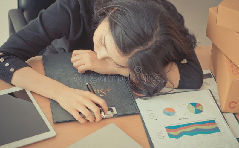 Mujer de la oficina que duerme sobre su escritorio de oficina imagen de archivo libre de regalías