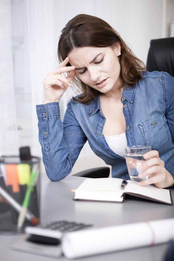 Mujer de la oficina que lee un libro con un vidrio de agua imagen de archivo