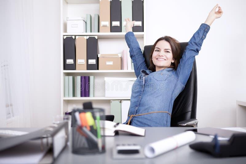 Mujer de la oficina que se sienta en la silla que estira sus brazos imagen de archivo