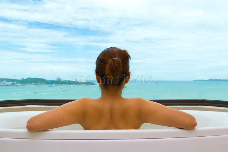Mujer de la parte trasera en bañera en la opinión del mar imágenes de archivo libres de regalías