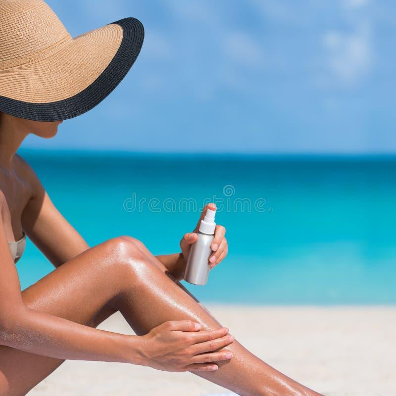 Mujer de la playa del cuidado de piel que toma el sol poniendo la protección solar fotos de archivo libres de regalías