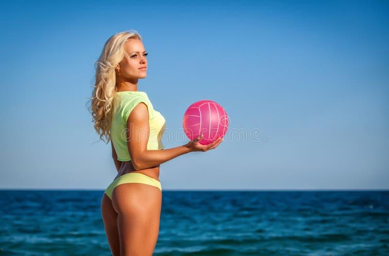 Mujer de la playa en el bikini que lleva a cabo un voleibol fotografía de archivo