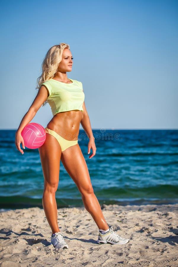Mujer de la playa en el bikini que lleva a cabo un voleibol fotos de archivo libres de regalías